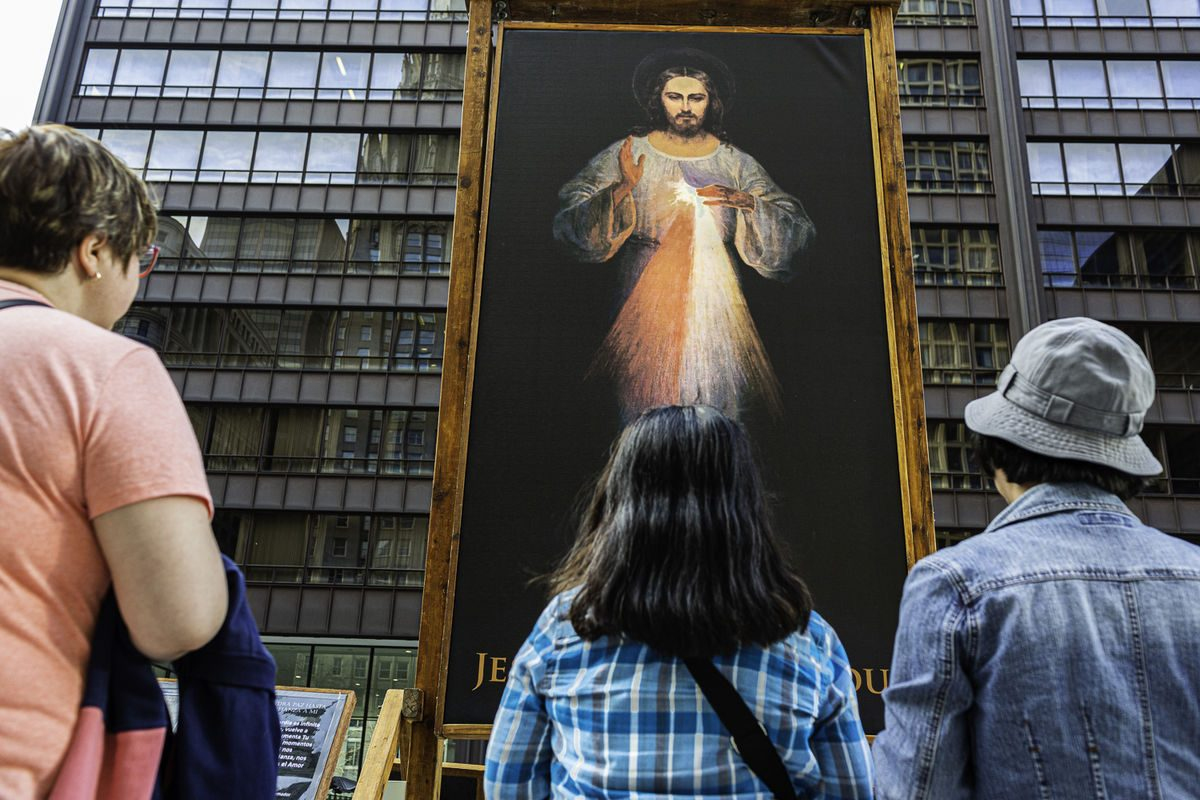 people look at jesus in a painting on the street.
