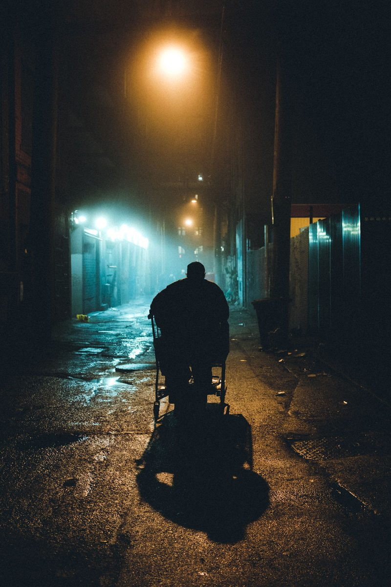 man with shopping cart in a dark street