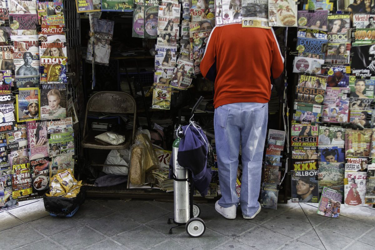 man with oxygen tank in front of a newsstand.